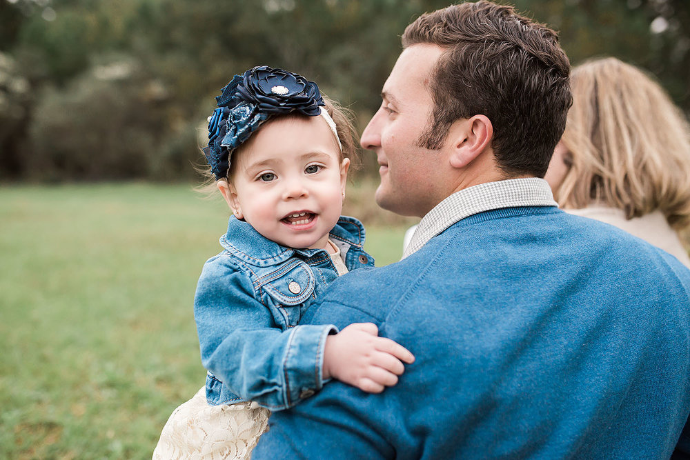 sweet baby girl on daddy's arm during Fall Portrait session