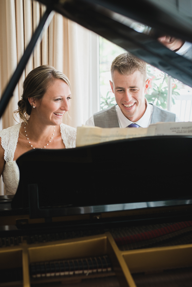 Happy bride and groom play piano