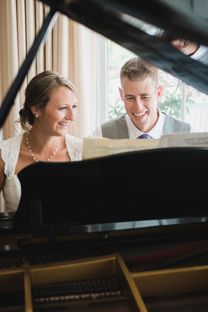 Happy bride and groom play piano