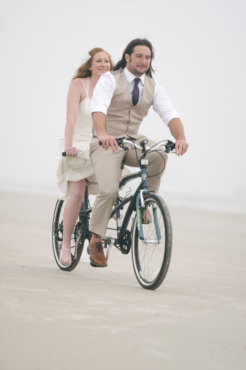 Couple rides bike on beach