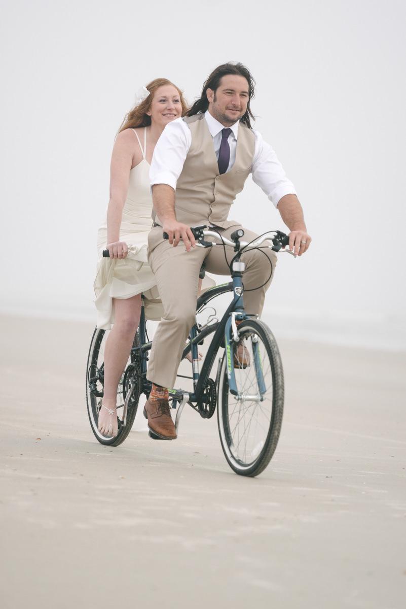 Couple rides bike on beach