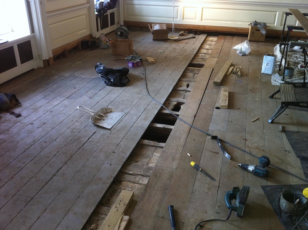 Carefully lifting and relaying the oak floor boards during the restoration process