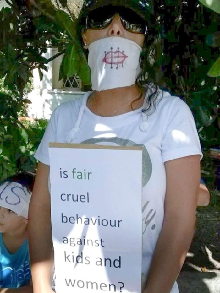 A protester on Nauru holds up a placard complaining about the treatment of women and children asylum seekers. Refugee Rights Action Network: Victoria Martin-Iverson Source: ABC.