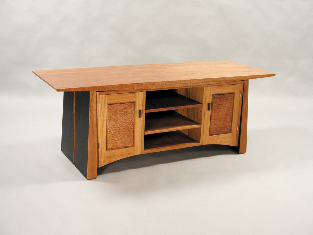 "This is the middle size of our entertainment pieces. With plenty of room for all of your equipment needs, in a little bit different configuration with some enclosed, and some open space. This one lends itself to a lot of different wood combinations.   Meander Entertainment Console #2       66""w x 24""h x 24""dp       $3,900    Shown in mahogany, pommelle sapele, and ebonized details"