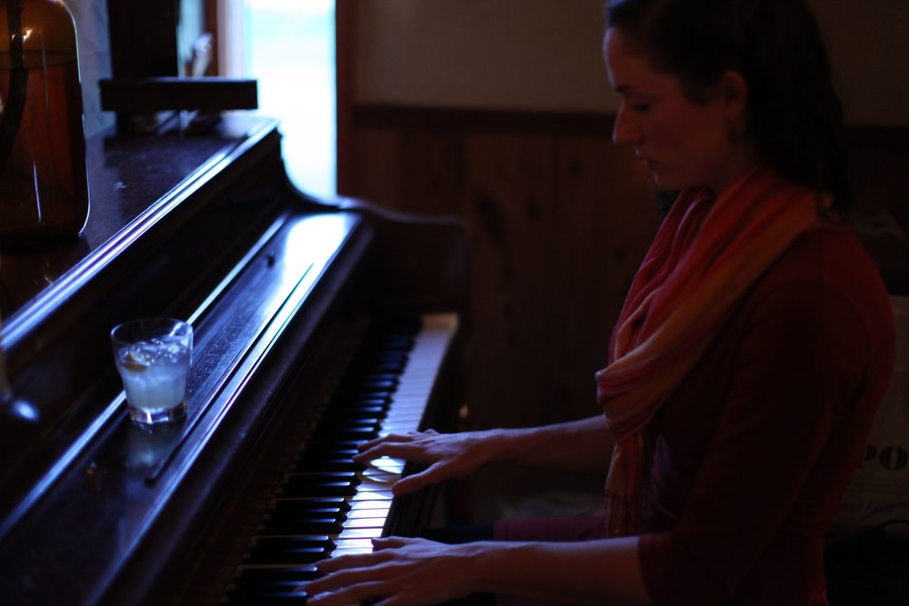 kaitlin at piano in community kitchen.jpg