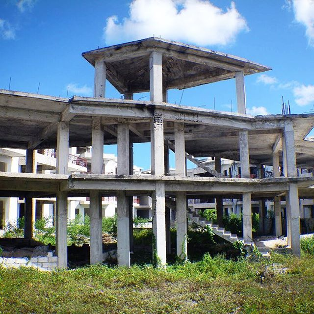 An unfinished building in the Dominican Republic 🏘During a two hour bus ride out of Punta Cana, we noticed many buildings still in the process of being built/half finished and abandoned. I learned later that this is only because building materials are so expensive. It may take years to finish building such a large structure, so their skeletons often become overgrown like this one.