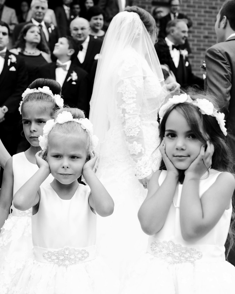 the flower girls cover their ears in response to the deafening sound of church bells. Ottawa.