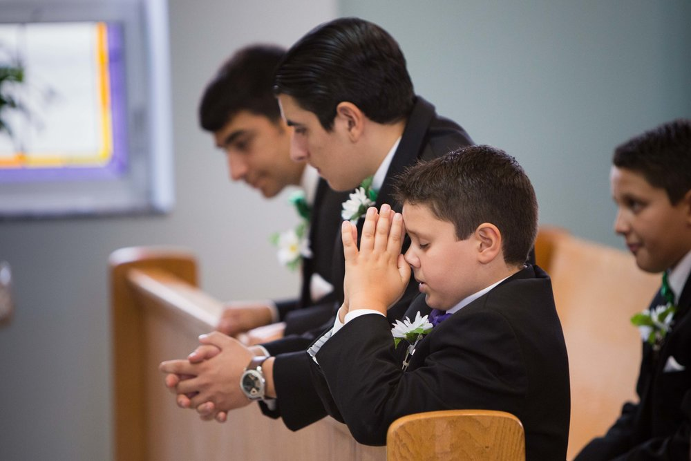 A boy prays for the newly weds.