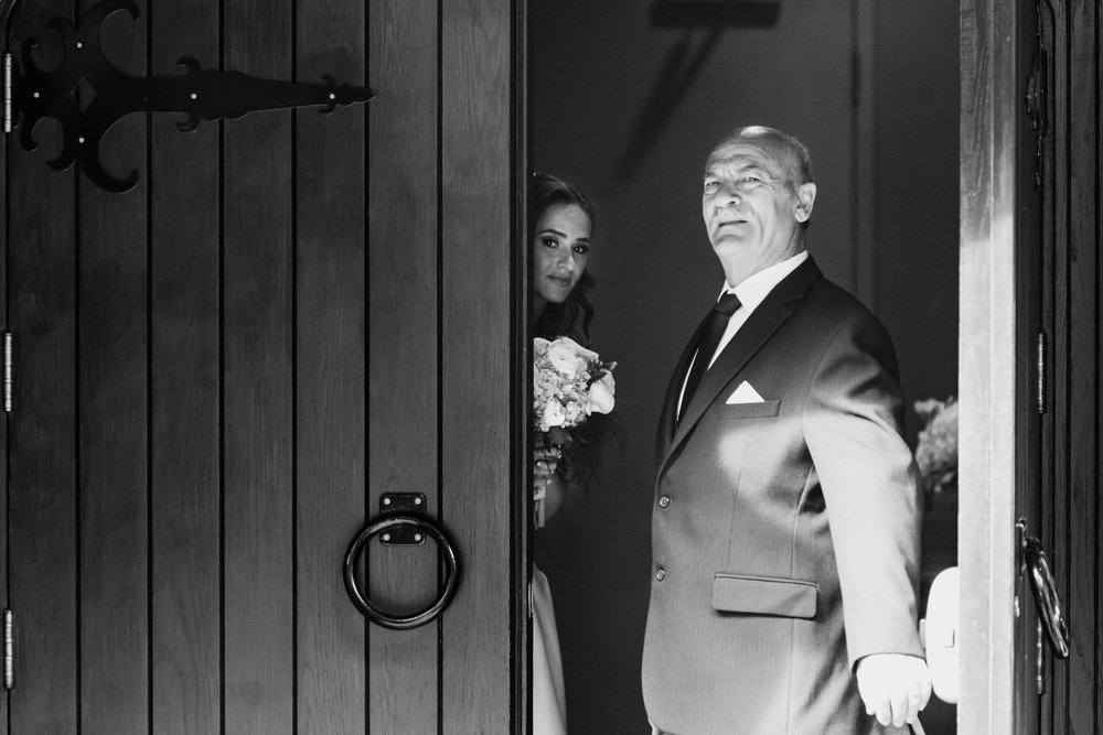 The father guards the door before walking the bride to the altar, Loch March golf club, Ottawa.