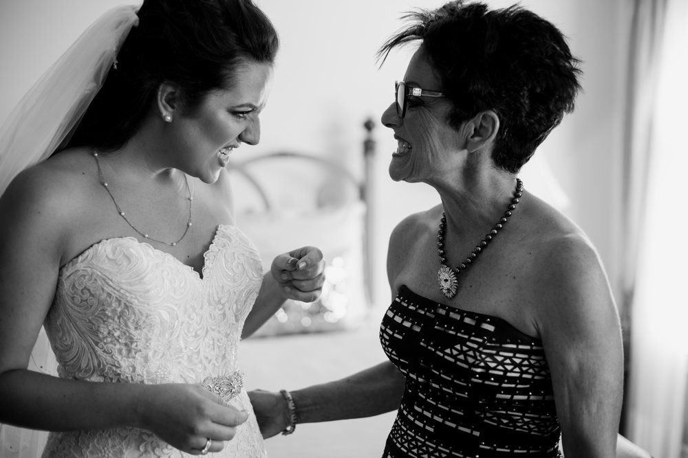 The bride and her mother were checking to see if there is anything on their teeth (probably). I raised the camera up while instinctively start turning the focusing ring, so by the time its at eye level the focus was pretty close to perfect, theres no need to recompose, and the moment was captured perfectly.