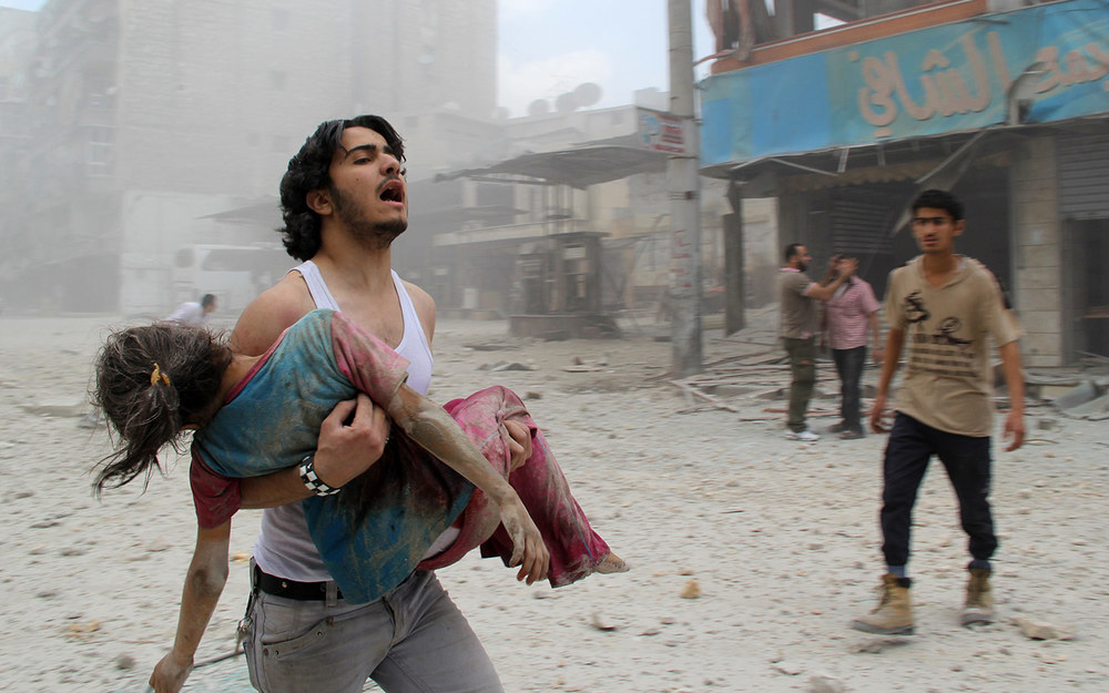 A man carries a young girl who was injured in a reported barrel-bomb attack by government forces in Aleppo / June 3rd 2014 /  BARAA AL-HALABI / AFP / GETTY IMAGES