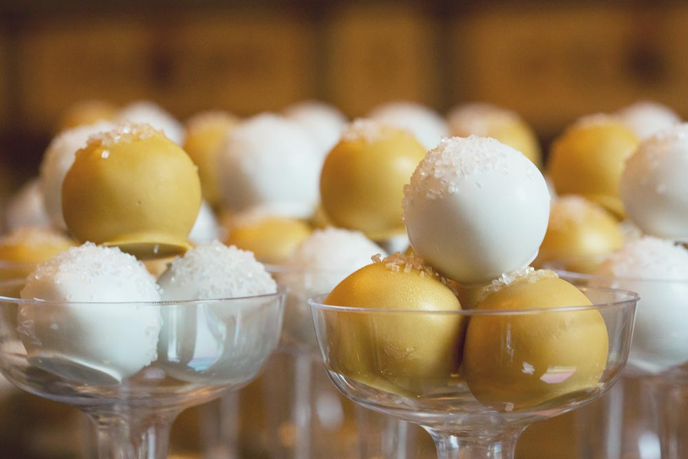 Gold and white cake balls served in champagne glasses to look like bubbles. Cake balls by   Sweets on a Stick  .