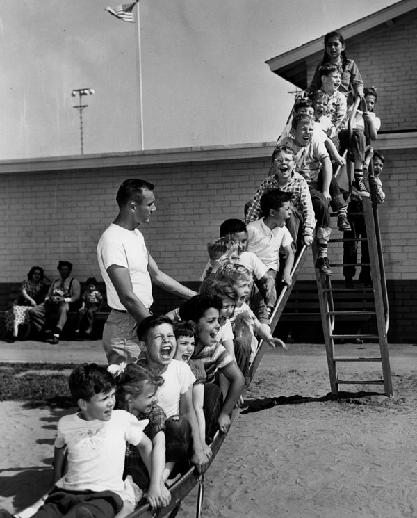 1951:  Normandie Playground SLIDE Jerry Jakway, recreation director at Normandie Playground, supervises a slideful of vacationing youngsters in the first full week of 1951 summer vacation. Hundreds of thousands of children are participating in a wide variety of special activities at the more than 100 municipal playgrounds. Photo dated: June 18, 1951.   [sourceHERALD EXAMINER]