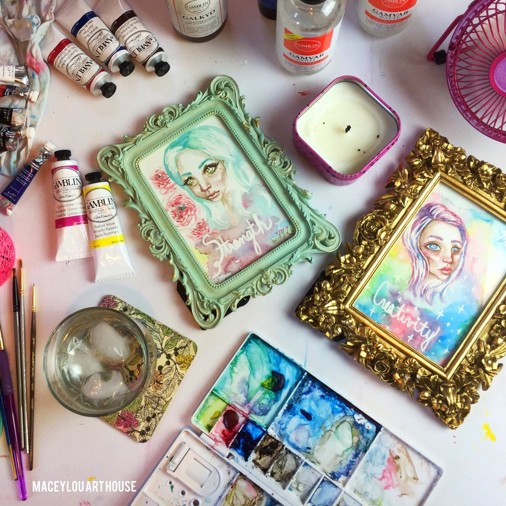 watercolor paintings in ornate frames on drawing desk