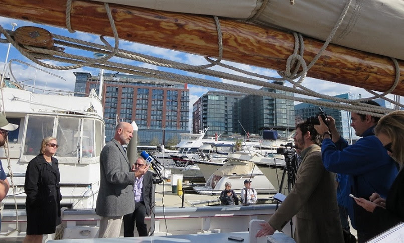 Greg Belanger, president of Ocean Passages, speaks before the media on the deck of the Harvey Gamage.