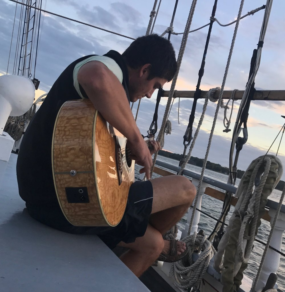Student Terence O'Brien playing guitar on the deck of the  Harvey Gamage