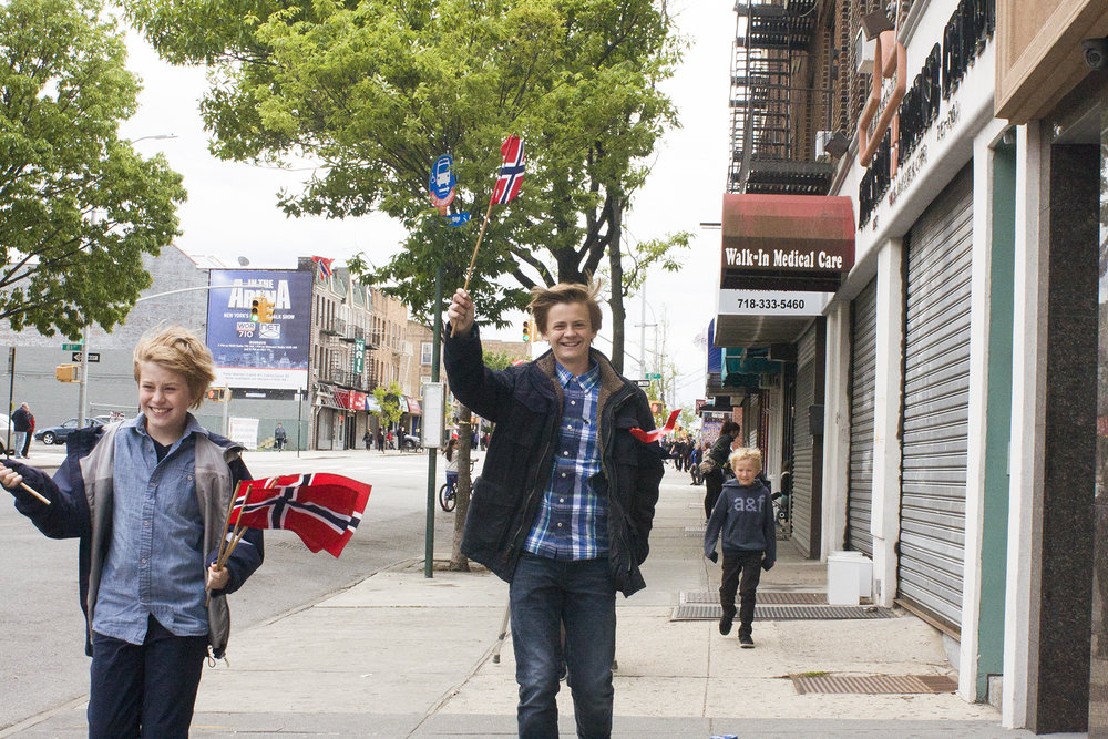 Three brothers have just purchased Norwegian flags from a street vendor before the start of the parade.