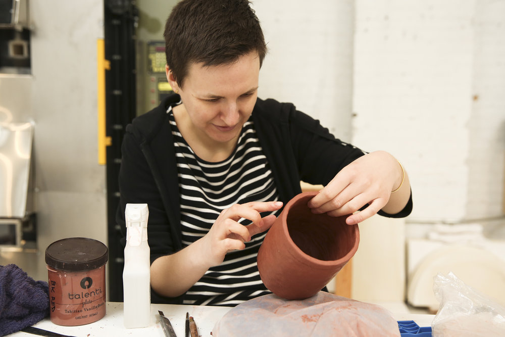 Karolina uses her finger to smooth slip onto the wet clay mug body. A gelato container full of slip (a mixture of clay and water) and a spray bottle of water to help join and bind sections of clay and evenly smooth over sections.