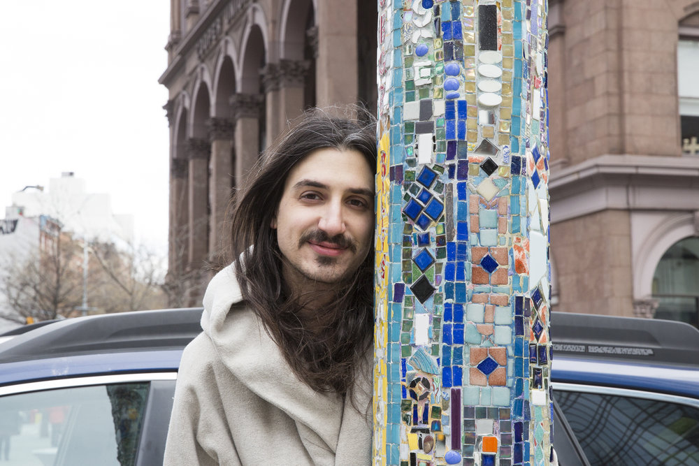 Aaron poses next to a decorated lamp post in Astor Place. These notable artworks are created by artist Jim Powers. Today Astor Place has 7 of the refurbished mosaic posts.