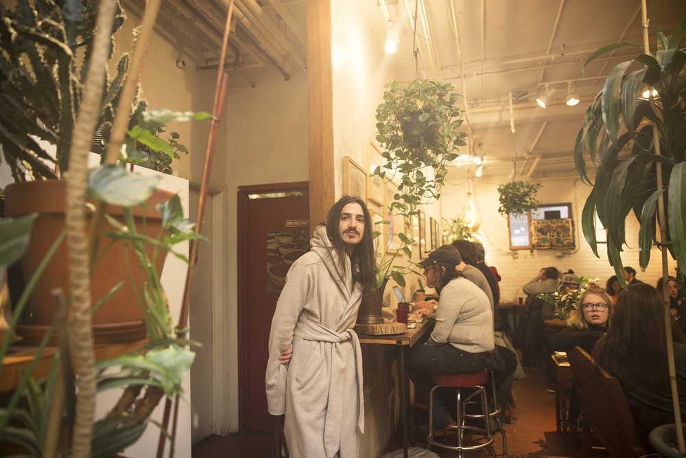 Aaron at Grounded Coffee House on Jane Street. With the space full of plants and floral arrangements, they find this space peaceful and often come here to work.