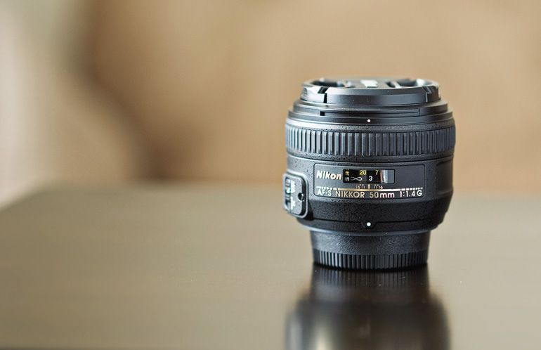 Photo of the new Nikon 50mm f/1.4G lens sitting on a table by an open window.