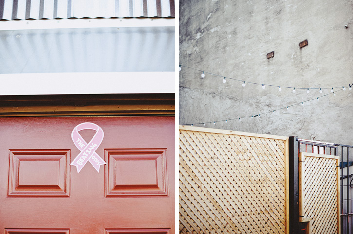 A red door with a breast cancer ribbon on it and a wooden gate with a string of lights above it in Downtown Des Moines