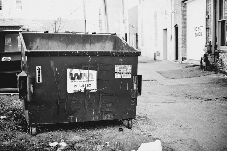 A dumpster in an alley in Downtown Des Moines with the words 'Vote Here' painted on it.