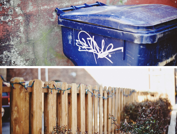 A garbage can with graffiti on it and Christmas lights strung along a wooden fence in downtown Des Moines.