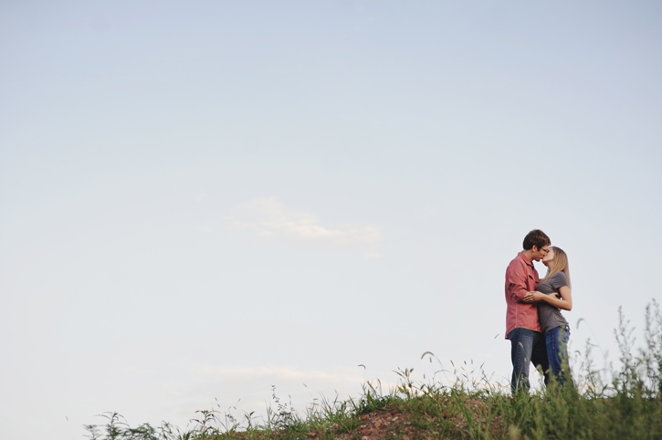 Lisa and Nathan kissing on top of a grassy hill in Des Moines with a blue sky background