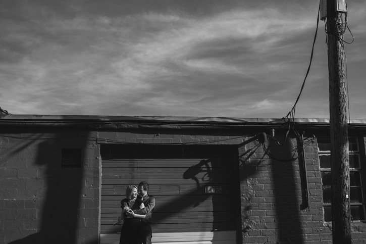 Bryan and Jill holding each other in front of a rustic garage in downtown Des Moines, Iowa