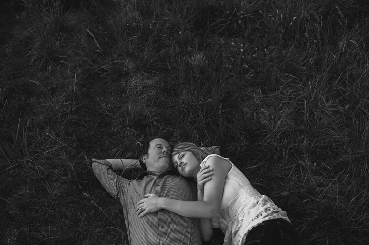Jill and Bryan laying together in a grassy field during their Des Moines, Iowa Engagement Session