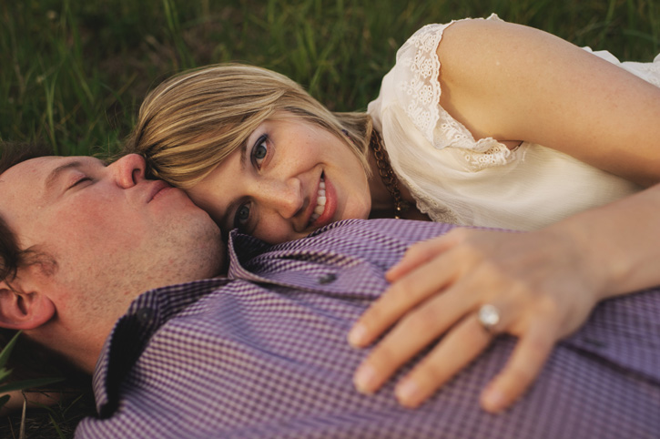 Jill resting her head on Bryans chest while laying in a field during their Des Moines, Iowa Engagement Session