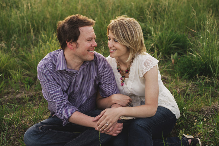 Bryan and Jill sitting in a field during their Des Moines, Iowa Engagement Session