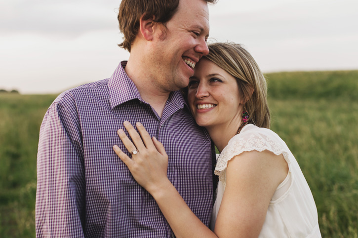 Jill grabbing Bryan and laughing during their engagement session in a field in Des Moines, Iowa.