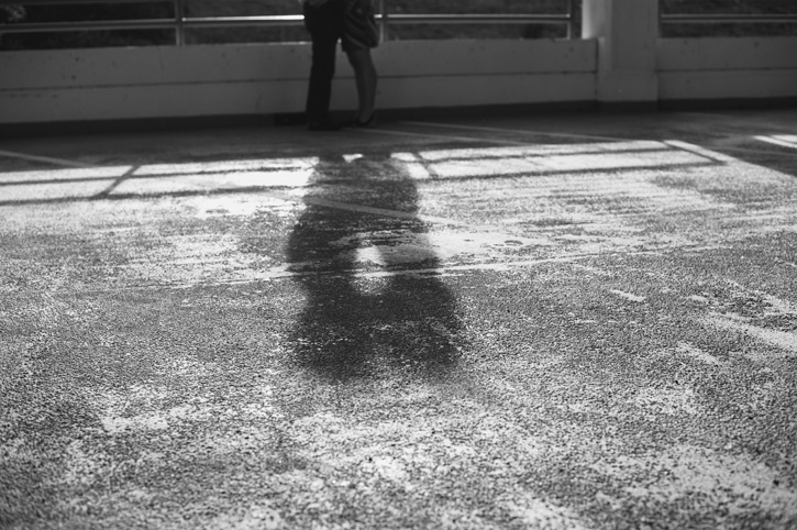 Jill and Bryan's shadows touching as they lean in for a kiss in a parking garage in downtown Des Moines, Iowa.