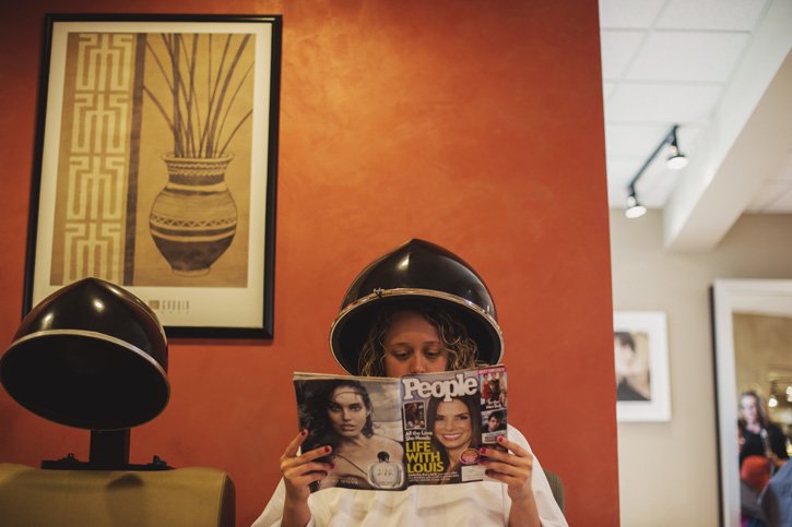 Laura's bridesmaid getting her hair done while reading a magazine at Estilo Salon in West Des Moines, Iowa