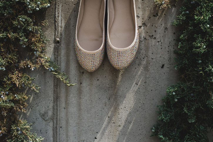 Laura's shoes hanging on a concrete wall surrounded by greenery at a Des Moines Wedding