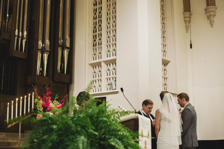 The pastor saying a prayer in front of Laura and Ryan at their church in Des Moines, Iowa