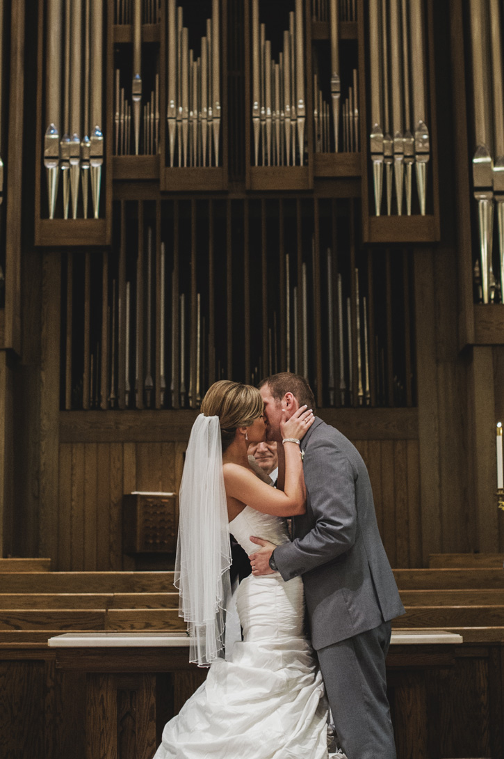 Laura and Ryan kissing as the happy couple at their church in Des Moines, Iowa