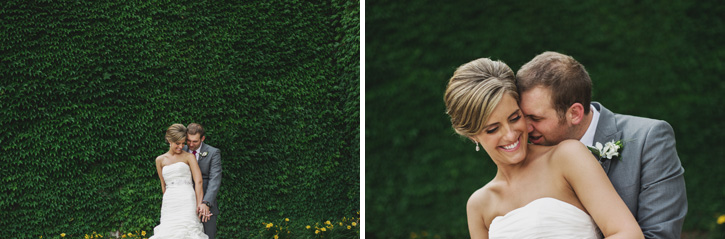 Laura and Ryan embracing in front of a leafy wall in Des Moines, Iowa by the Wells Fargo Arena