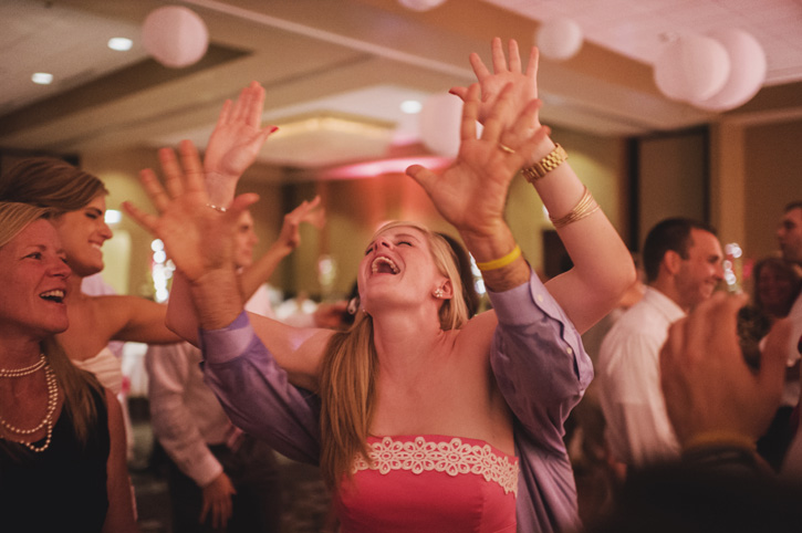 A groomsman dancing with drinks during the reception at Embassy Suites in Des Moines, Iowa