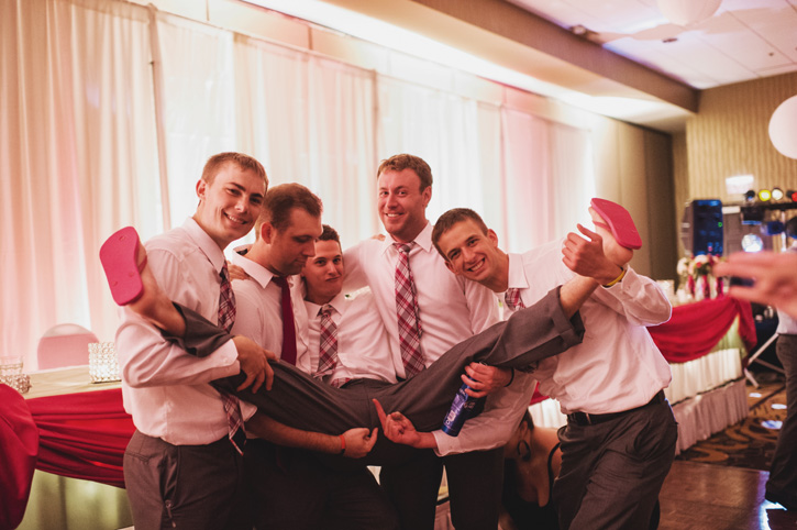 Groomsmen picking each other up during the reception at Embassy Suites in Des Moines, Iowa