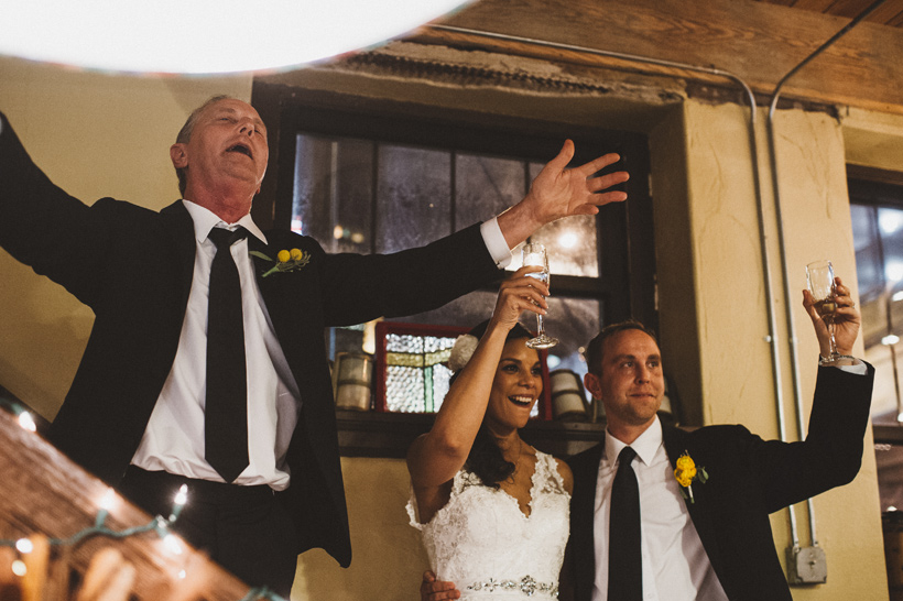 Adam's family sings a family song during the reception at West End Architectural Salvage | Des Moines Wedding Photographer Brian Davis