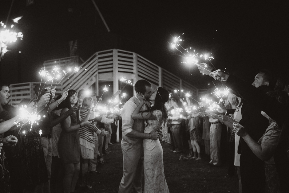 Ashley and Chad share a kiss during their sparkler exit from their wedding in Maquoketa, IA