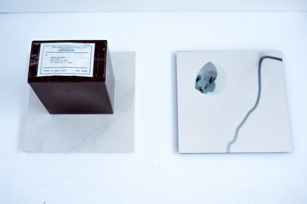 Left to right:  Performance , 2016, cremains of artist's brother, label, and marble tile, 11.75 x 11.75 x 10.25 inches, and,  Brother: Absent , 2016, polarized lens, magnified lens, false eyelash, butterfly wing, mirror, and ceramic tile, 12 x 12 x 2.5 inches