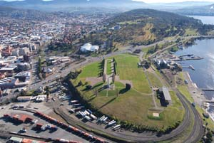 6 Futurist remembrance: An Acconci footbridge for Hobart? - DANIEL THOMAS    Aerial view looking northwest along the spine of the Queens Domain. The proposed Acconci bridge seeks to connect the Cenotaph (centre foreground) with the Avenue of Honour (cleared yellow-tinged native grassland in the middle ground); image courtesy Inspiring Place, Hobart; photo: Adam Muyt, Hobart City Council