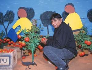 8 Obituary: Ian W. Abdulla (1947-2011) JOHN KEAN   Ian Abdulla in his installation  Picking tomatoes in the hot sun  , 2001, Melbourne Museum. Image courtesy Museum Victoria. Photograph by Jon Augier.