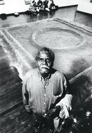 8 Jimmy Wululu (1936-2005) Bark painter from Arnhem Land: DJON MUNDINE   Jimmy Wululu with Bongu (waterhole) sand sculpture at the ANU Drill Hall Gallery, Canberra, 1992. Photo courtesy of  The Canberra Times
