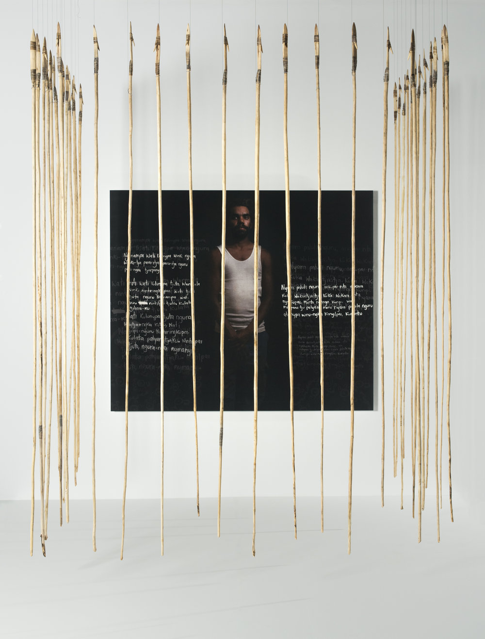 Anwar Young, Unrupa Rhonda Dick and Frank Young,  Kulata Tjuta – Wati kulunypa tjukurpa (Many spears – Young fella story) , 2017, digital print, wood, kangaroo tendon,  kiti  (natural glue); print 148 x 176cm; spears 280 x 2 x 2cm approx. (37 pieces); image courtesy the artists and the Museum and Art Gallery of the Northern Territory, Darwin