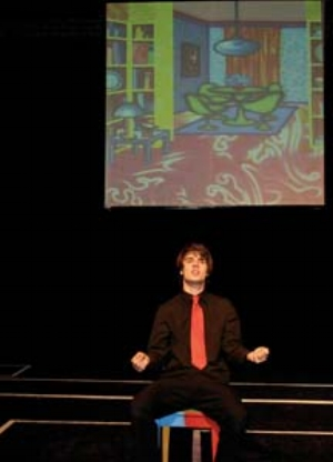 8 Fluorescent Facade: Arkley in Action: ODETTE KELADA   Patrick McCarthy in character(s), scene from  Fluorescent Facade,  with a projection of Howard Arkley's Mod Style, 1992. Photograph by Mary Evans